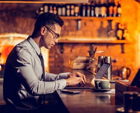 Businessman working remotely sitting at the bar stand