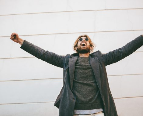 Portrait of a successful bearded man wearing sunglasses and coat standing on a city street with outstretched hands