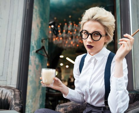 Serious young woman in round glasses smoking cigarette and drinking coffee in cafe